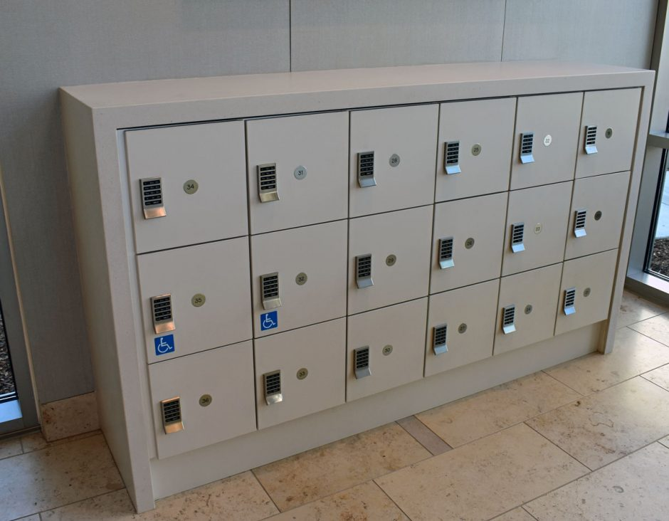 Corian locker enclosures are located in the lobby area behind the reception desk.