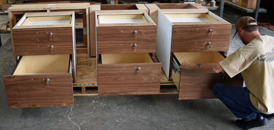 Plain sliced walnut veneer is featured on the drawers and drawer fronts for the reception desk in the atrium lobby.