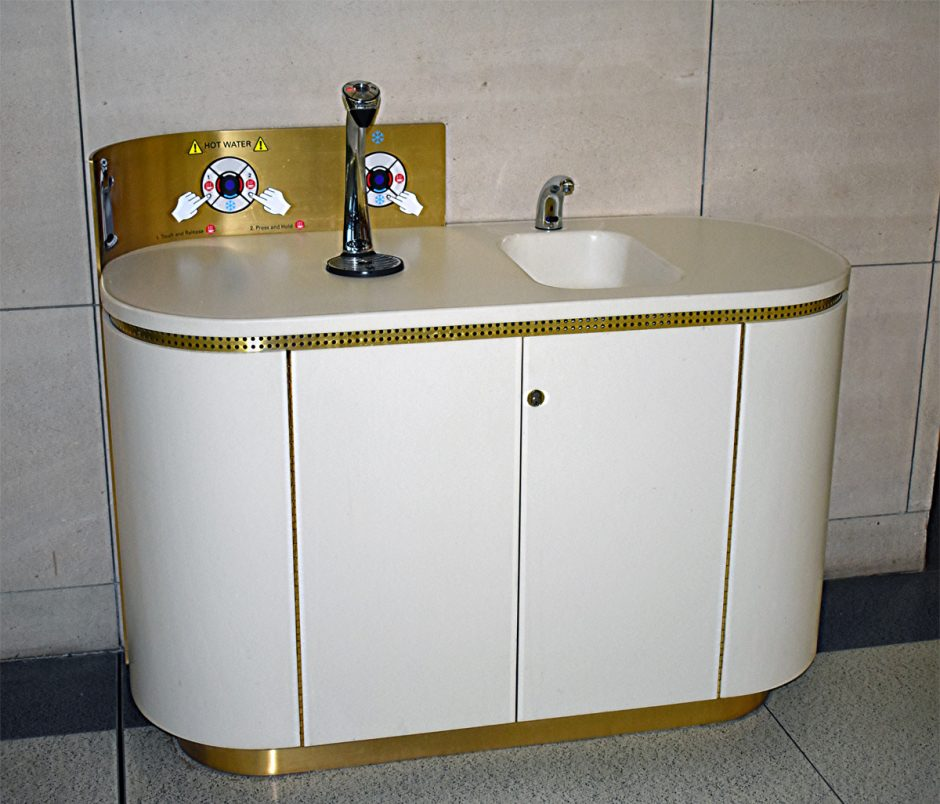 The hydration stations feature white corian with brass toe kicks.